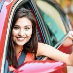 teen leaning out of her car's driver side window, teen auto insurance costs
